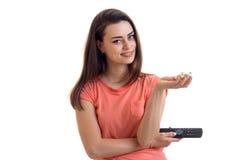 Το χαριτωμένο κορίτσι με τον τηλεχειρισμό κρατά στην παλάμη pop-corn χεριών σας εξετάζει τη κάμερα και το χαμόγελο Στοκ φωτογραφίες με δικαίωμα ελεύθερης χρήσης
