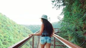 Το χαριτωμένο κορίτσι με τους πολύ ευθείς μαύρους περιπάτους τρίχας στην ξύλινη γέφυρα πέρα από το φαράγγι Okatce, φίλαθλη κυρία  απόθεμα βίντεο