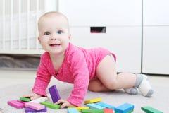 Το χαριτωμένο κορίτσι 6 μηνών παίζει το ξύλινο πολύχρωμο meccano στο σπίτι Στοκ Εικόνες