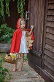 Το χαριτωμένο κορίτσι παιδιών παίζει λίγη κόκκινη οδηγώντας κουκούλα στο θερινό κήπο Στοκ Εικόνες