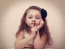 Το χαριτωμένο κορίτσι παιδιών που παρουσιάζει σιωπή υπογράφει το δάχτυλο κοντά στα χείλια Τρύγος Στοκ Φωτογραφία