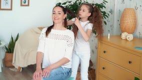 Το χαριτωμένο κορίτσι πλέκει την τρίχα mom της στην πλεξούδα, σε αργή κίνηση απόθεμα βίντεο