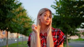Το χαριτωμένο κορίτσι πορτρέτου με τη μακριά άσπρη τρίχα στο κόκκινο ελεγμένο πουκάμισο είναι αμφιβολίες και κοιτάζει επίμονα στη απόθεμα βίντεο