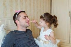 Το χαριτωμένο κορίτσι που βάζει αποτελεί στον πατέρα της Στοκ Εικόνες
