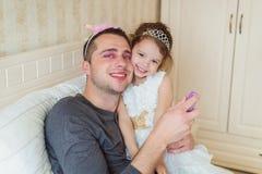 Το χαριτωμένο κορίτσι που βάζει αποτελεί στον πατέρα της Στοκ φωτογραφία με δικαίωμα ελεύθερης χρήσης
