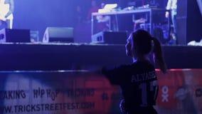 Το χαριτωμένο κορίτσι που φορά τη μαύρη μπλούζα θερμαίνει πριν από την απόδοση δίπλα στο στάδιο απόθεμα βίντεο