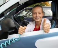Το χαριτωμένο κορίτσι στο ηλεκτρικό αυτοκίνητο και εμφανίζει ΕΝΤΆΞΕΙ. Στοκ Εικόνες