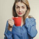 Το χαριτωμένο κορίτσι στο μπλε πουκάμισο πίνει τον καφέ Στοκ Εικόνα