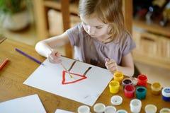 Το χαριτωμένο κορίτσι σύρει με τα χρώματα στον παιδικό σταθμό στοκ φωτογραφία με δικαίωμα ελεύθερης χρήσης