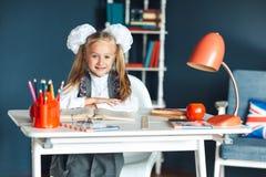 Το χαριτωμένο κορίτσι blondy στη σχολική στολή με το λευκό υποκύπτει τη συνεδρίαση στο γραφείο και τη μελέτη στο σπίτι r στοκ φωτογραφίες