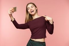 Το χαριτωμένο κορίτσι brunette παίρνει ένα selfie Χαμογελά ευρέως Έχει τη μακριά κυματιστή τρίχα brunette Κορίτσι ομορφιάς στο ρο Στοκ εικόνα με δικαίωμα ελεύθερης χρήσης