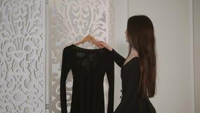 Το χαριτωμένο κορίτσι brunette πλησιάζει για να ντύσει σε μια κρεμάστρα στο σαφές δωμάτιό της απόθεμα βίντεο