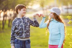 Το χαριτωμένο κράτημα παιδιών παραδίδει μια μορφή καρδιών την άνοιξη υπαίθρια στοκ φωτογραφία