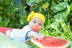 Το χαριτωμένο λατρευτό κοριτσάκι μπλε ματιών 6 μήνες παίρνει έξω μισό καρπούζι στο υπόβαθρο του φυλλώματος ημέρα ηλιόλουστη Στοκ Εικόνα