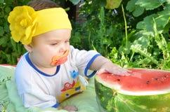 Το χαριτωμένο λατρευτό κοριτσάκι μπλε ματιών 6 μήνες παίρνει έξω μισό καρπούζι στο υπόβαθρο του φυλλώματος ημέρα ηλιόλουστη Στοκ εικόνες με δικαίωμα ελεύθερης χρήσης