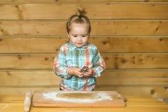 Το χαριτωμένο μαγείρεμα παιδιών με τη ζύμη και το αλεύρι, κρατά τη μεταλλική φόρμα Στοκ Εικόνα
