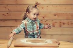 Το χαριτωμένο μαγείρεμα παιδιών με τη ζύμη και το αλεύρι, κρατά τη μεταλλική φόρμα Στοκ εικόνες με δικαίωμα ελεύθερης χρήσης