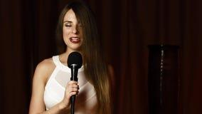 Το χαριτωμένο μακρυμάλλες κορίτσι στο άσπρο φόρεμα κρατά mic και τραγουδά με το θεαματικό χαμόγελο φιλμ μικρού μήκους