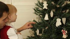 Το χαριτωμένο μικρό κορίτσι διακοσμεί το χριστουγεννιάτικο δέντρο απόθεμα βίντεο