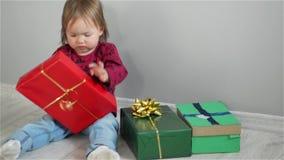Το χαριτωμένο μικρό κορίτσι κάθεται κοντά στα φωτεινά κιβώτια και το κορίτσι ανοίγει τα δώρα Το μωρό με το ενδιαφέρον εξετάζει τα φιλμ μικρού μήκους