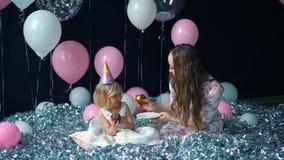 Το χαριτωμένο μικρό κορίτσι και το όμορφο νέο mom της τρώνε cupcakes, γιορτή γενεθλίων, κόμμα διακοπών Στο υπόβαθρο των μπαλονιών απόθεμα βίντεο
