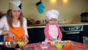 Το χαριτωμένο μικρό κορίτσι και το όμορφο mom στις ποδιές παίζουν ζυμώνοντας τη ζύμη απόθεμα βίντεο