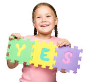 Το χαριτωμένο μικρό κορίτσι κρατά ναι το σύνθημα στοκ φωτογραφίες