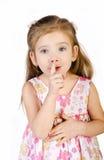 Το χαριτωμένο μικρό κορίτσι κρατά το δάχτυλό της κοντά στο στόμα που απομονώνεται στοκ φωτογραφία με δικαίωμα ελεύθερης χρήσης