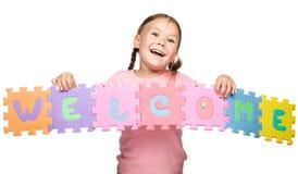 Το χαριτωμένο μικρό κορίτσι κρατά το ευπρόσδεκτο σύνθημα στοκ εικόνες