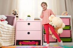 Το χαριτωμένο μικρό κορίτσι με μεγάλο έναν teddy αφορά το πάτωμα στοκ εικόνες