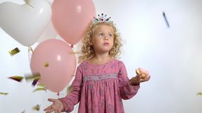 Το χαριτωμένο μικρό κορίτσι με τα μπαλόνια τρώει doughnut στα γενέθλιά της, που απομονώνονται πέρα από το άσπρο υπόβαθρο φιλμ μικρού μήκους