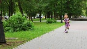 Το χαριτωμένο μικρό κορίτσι με την κόκκινη τρίχα οδηγά το μηχανικό δίκυκλο στο πράσινο θερινό πάρκο απόθεμα βίντεο