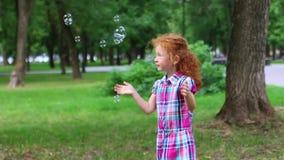 Το χαριτωμένο μικρό κορίτσι με την κόκκινη τρίχα πιάνει τις φυσαλίδες στο πράσινο θερινό πάρκο φιλμ μικρού μήκους