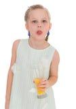 Το χαριτωμένο μικρό κορίτσι πίνει το χυμό από πορτοκάλι Στοκ Εικόνες