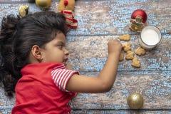 Το χαριτωμένο μικρό κορίτσι παίζει με τα μπισκότα και το γάλα Santas σε Chr στοκ φωτογραφίες