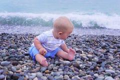 Το χαριτωμένο μικρό κορίτσι παίζει με τον κάδο σε μια παραλία, που συλλέγει τη φωτογραφία βράχων Στοκ Φωτογραφίες