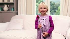 Το χαριτωμένο μικρό κορίτσι που κρατά ένα κόκκινο αυξήθηκε απόθεμα βίντεο