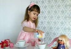 Το χαριτωμένο μικρό κορίτσι που παίζει με την κούκλα Στοκ εικόνες με δικαίωμα ελεύθερης χρήσης