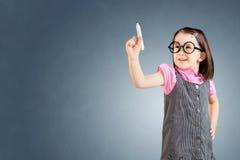 Το χαριτωμένο μικρό κορίτσι που φορά το επιχειρησιακό φόρεμα και επισύρει την προσοχή κάτι στην εικονική οθόνη πρόσκληση συγχαρητ Στοκ φωτογραφίες με δικαίωμα ελεύθερης χρήσης