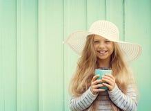 Το χαριτωμένο μικρό κορίτσι στέκεται κοντά σε έναν τυρκουάζ τοίχο στο άσπρο φλυτζάνι καπέλων και εκμετάλλευσης Διάστημα για το κε Στοκ Εικόνα