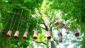 Το χαριτωμένο μικρό κορίτσι στην αναρρίχηση του εξοπλισμού ασφάλειας σε ένα σπίτι δέντρων ή σε ένα πάρκο σχοινιών αναρριχείται στ φιλμ μικρού μήκους