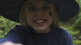 Το χαριτωμένο μικρό κορίτσι στην εξάρτηση μαγισσών που κατασκευάζει τη τρομακτική κάμερα προσώπων, προσποίηση δημιουργεί απόθεμα βίντεο