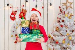 Το χαριτωμένο μικρό κορίτσι στην κόκκινη εκμετάλλευση καπέλων παρουσιάζει στοκ φωτογραφία με δικαίωμα ελεύθερης χρήσης