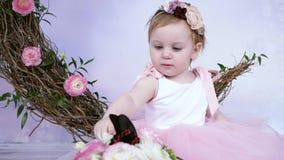 Το χαριτωμένο μικρό κορίτσι στο ρόδινο φόρεμα δείχνει στη ζωντανή μεγάλη πεταλούδα στο άσπρο υπόβαθρο με το ντεκόρ στο εσωτερικό απόθεμα βίντεο