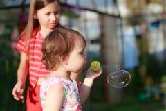 Το χαριτωμένο μικρό κορίτσι φυσά ένα σαπούνι βράζει στοκ εικόνες