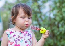 Το χαριτωμένο μικρό κορίτσι φυσά ένα σαπούνι βράζει στοκ φωτογραφία με δικαίωμα ελεύθερης χρήσης