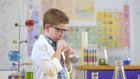 Το χαριτωμένο μικρό παιδί κάνει το πείραμα με το υγρό στο εργαστήριο απόθεμα βίντεο