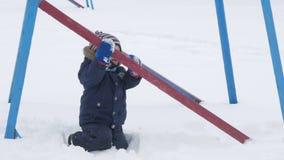 Το χαριτωμένο μικρό παιδί και η νέα μητέρα παίζουν το χειμώνα με το χιόνι στο πάρκο Μπλε σακάκι και κόκκινο παιδιών ` s στο mom φιλμ μικρού μήκους