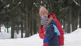 Το χαριτωμένο μικρό παιδί και η νέα μητέρα παίζουν το χειμώνα με το χιόνι στο πάρκο Μπλε σακάκι και κόκκινο παιδιών ` s στο mom απόθεμα βίντεο