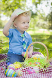 Το χαριτωμένο μικρό παιδί έξω από τα αυγά Πάσχας εκμετάλλευσης τοποθετεί αιχμή στο καπέλο του στοκ φωτογραφίες με δικαίωμα ελεύθερης χρήσης